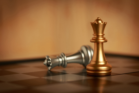 Two queen chess set on board. The gold is located and silver falls down. Select focus shallow depth of field and blurred background. Concept work and retro process