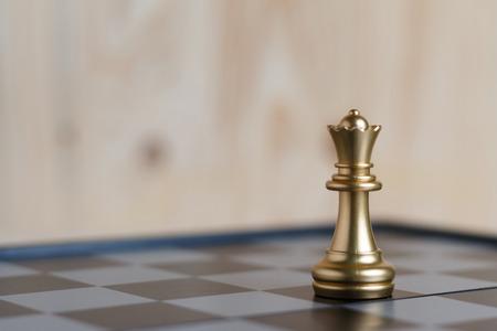 Das an Bord befindliche Goldkönigin-Schachspiel befindet sich. Wählen Sie die geringe Schärfentiefe des Fokus und den unscharfen Hintergrund. Konzeptarbeit