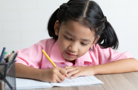 Gros plan, la petite fille fait ses devoirs avec bonheur. Les enfants utilisent un crayon jaune pour écrire un cahier sur la table en bois.