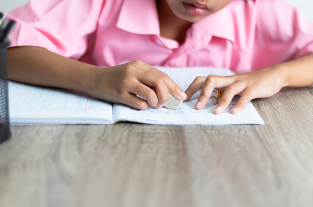 Children use a eraser is deleting words. Close up the little girl is doing homework on the wooden table. Banco de Imagens