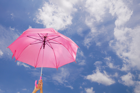 two hand are holding a umbrella on blue sky background with copy space in concept