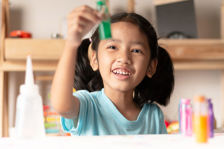 The little girl is testing color in glass and looking with smile and happiness. Select focus shallow depth of fied. Banque d'images