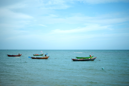 Five small fishing boat parking on the sea with blue sky background