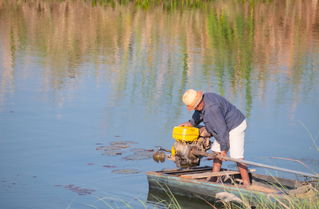 Old boatman brought the small boat with motor from the shore into the river. Stock Photo