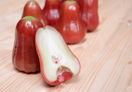 Close up half rose apple on the wooden table with copy space.Syzygium is a genus of flowering plants. That can be eaten.
