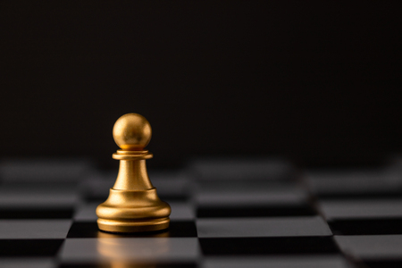 gold chip on the chessboard and black background