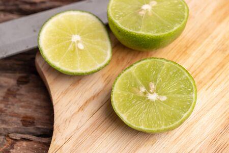 Chiudere metà del lime verde e seminare con un coltello posto su una tavola di legno in una cucina. Il limone è una specie di frutto. Il risultato è molto acido. Organizzato nel genere Arancio e verde a maturazione è giallo con buccia sottile, all'interno i petali sono molto umidi, suddivisi in frutti pregiati. Comunemente usato come condimento È anche considerato nutriente e medico.