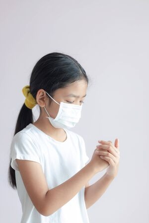 The Asian little girl wears a medical protective mask. The child is rubbing her hands with alcohol gel on her palm to clean. Prevention for Coronavirus or COVID-19. Reklamní fotografie