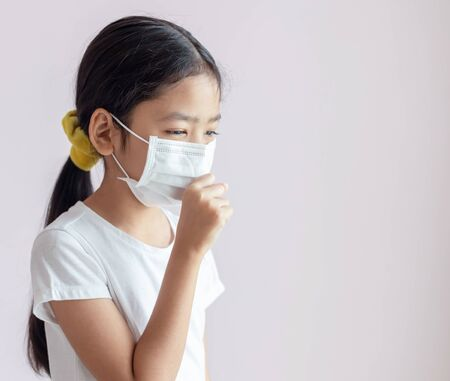 Portrait of Children wearing sanitary masks and coughs. The epidemic of the flu, Coronavirus or COVID-19 and illness with smog. Stock Photo