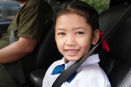 Asian girl wear school uniform sit in the car and fasten the belt for safety. The students sitting with the parents.