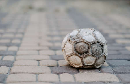 Old soccer ball lies on the ground, abstraction.