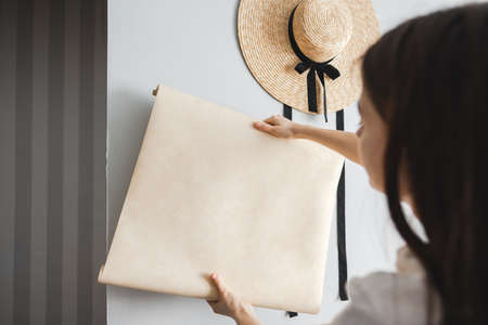House repair, woman chooses new wallpaper for her apartment, interior design. High quality photo 写真素材
