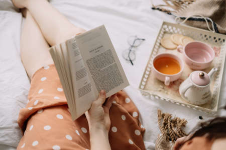 A woman reads a book at home in bed and drinks tea, home leisure in coziness and comfort. High quality photo