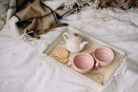 Kettle with tea and cups on a tray. Breakfast at home in bed, comfort and coziness. High quality photo