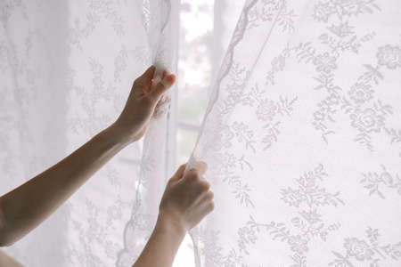 Woman closes lace curtains in bedroom, close-up. Domestic life. High quality photo 写真素材