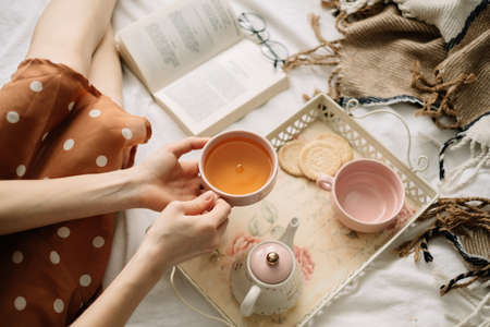 A woman holds a cup of hot tea on the bed at home and reads a book, home leisure in coziness and comfort. High quality photo