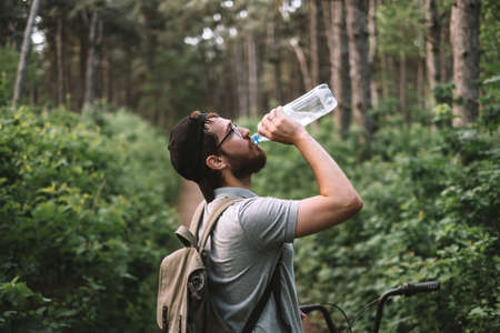 A young male cyclist drinks water from a plastic bottle at a halt in the forest. Tourism, active lifestyle. High quality photo