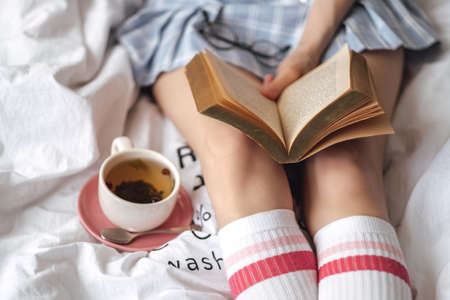 Young caucasian woman sitting on a white bed at home reading a book and drink tea. High quality photo