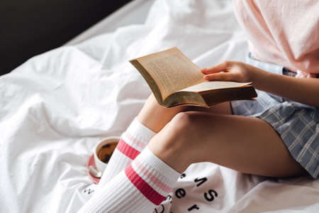 Woman sitting on a white bed at home and reading book and drink tea.
