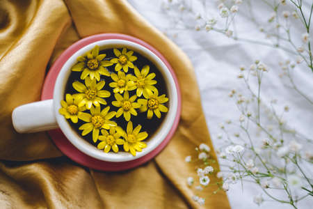 Cup with yellow flowers on a golden textile. Spring background.