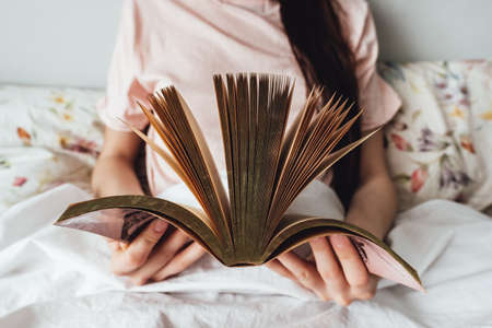 Woman holds open book in hands, lying in bed at home.
