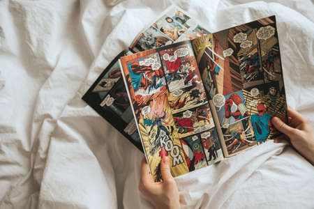 Woman reads comics in bed at home.