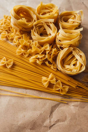 Varieties of Italian pasta. Spaghetti, farfalle and tagliatelle isolated on a white background, top view. Non-perishable food.