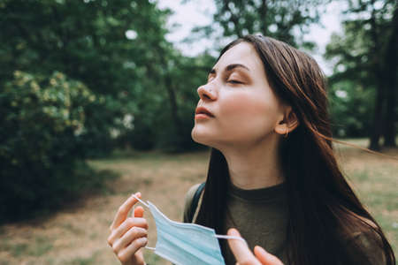Young caucasian pretty woman removes a medical protective mask from her face on nature, surrounded by trees, breathing clean fresh air. High quality photo Foto de archivo