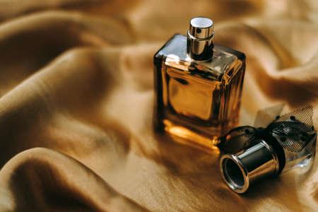 Perfume bottle on golden satin fabric, close-up, warm light. High quality photo