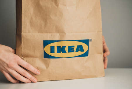 Hands holding craft paper shopping bag with IKEA logo. High quality photo