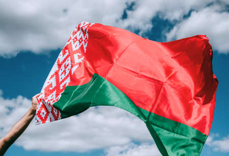 Belarus flag in hand on blue sky background. High quality photo