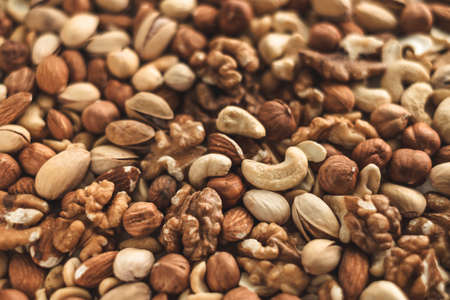 Different types of nuts, nut mix of almonds, hazelnuts, cashews, peanuts texture background. Close up. High quality photo