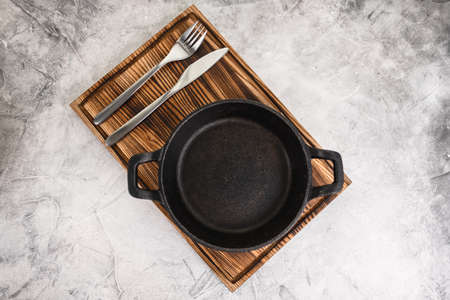 Empty black pan plate on a wooden board with cutlery on a gray background. High quality photo
