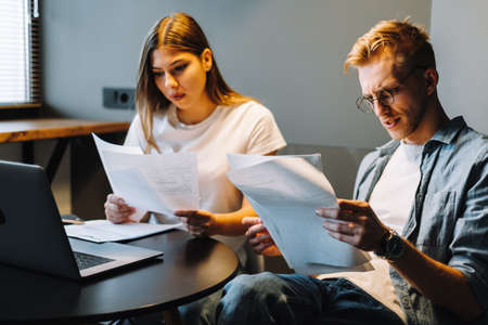 Worried young couple manages finances by looking through their bank accounts in the living room at desk using laptop. Woman and man look at documents together. Planning budget expenses.
