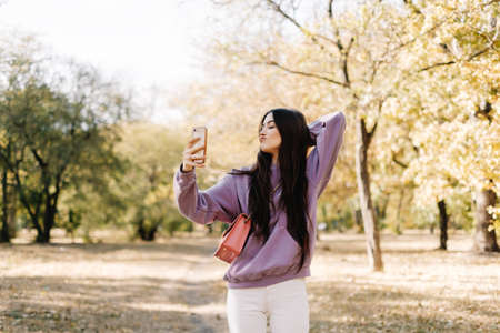 Beautiful young woman making selfie using smartphone and enjoying autumn weather in the park. Woman walking in the autumn park. High quality photo