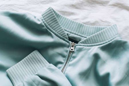 Light turquoise women's jacket with zip, close-up. Pastel colors. High quality photo 免版税图像