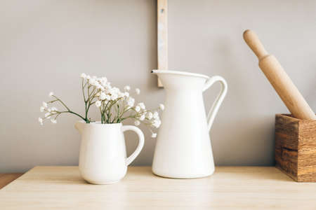 White jug and flowers in a vase on a wooden table in the kitchen. High quality photo