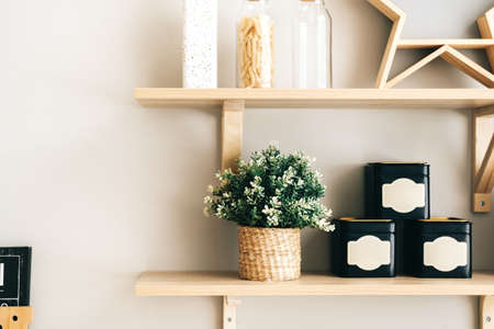Grocery and kitchenware on the wooden shelves in modern bright kitchen. High quality photo