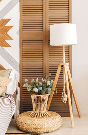 Wooden floor lamp and plants near the bed, interior design detail. High quality photo Banque d'images