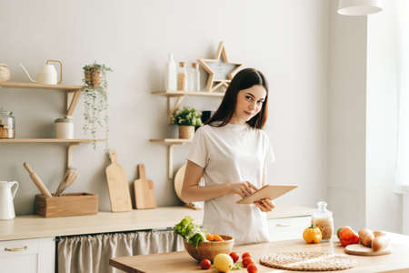 Young caucasian woman use tablet computer in the modern kitchen, preparing salad, read recipe.