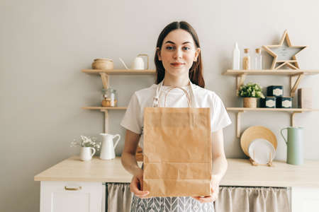 Young woman holds eco shopping paper bag with food and vegetables in hands, while standing in modern kitchen. Delivery food, take away.