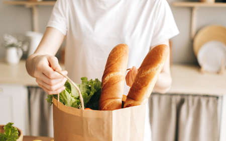 Caucasian woman hold eco shopping bag with fresh vegetables and baguette in modern kitchen. High quality photo