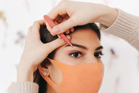 Eyebrow shaping procedure, make-up master uses tweezers to shape the eyebrows. High quality photo Stock Photo