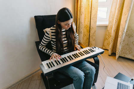 Young caucasian woman learns to play the piano keys using a laptop at home distantly. High quality photo Stock Photo