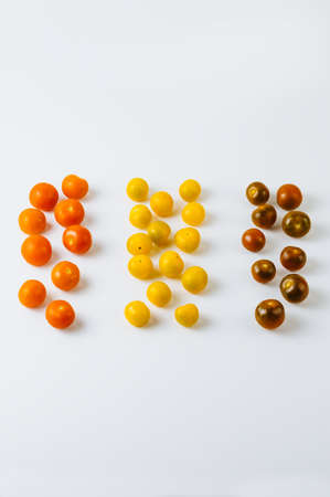 Varieties of cherry tomatoes in line isolated on white background, abstraction.
