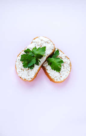 White pate spread on two slices of bread and decorated with parsley isolated on white background.