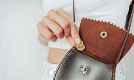 Girl puts a coin in the leather purse, on a white background.