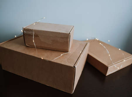 Cardboard boxes on a wooden table with garland.