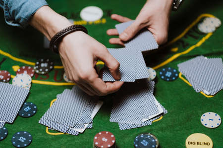 Croupier holds playing cards, game chips on the table. Poker concept.