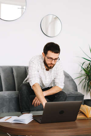 Young caucasian businessman work at home, freelance work, use laptop computer. High quality photo Zdjęcie Seryjne